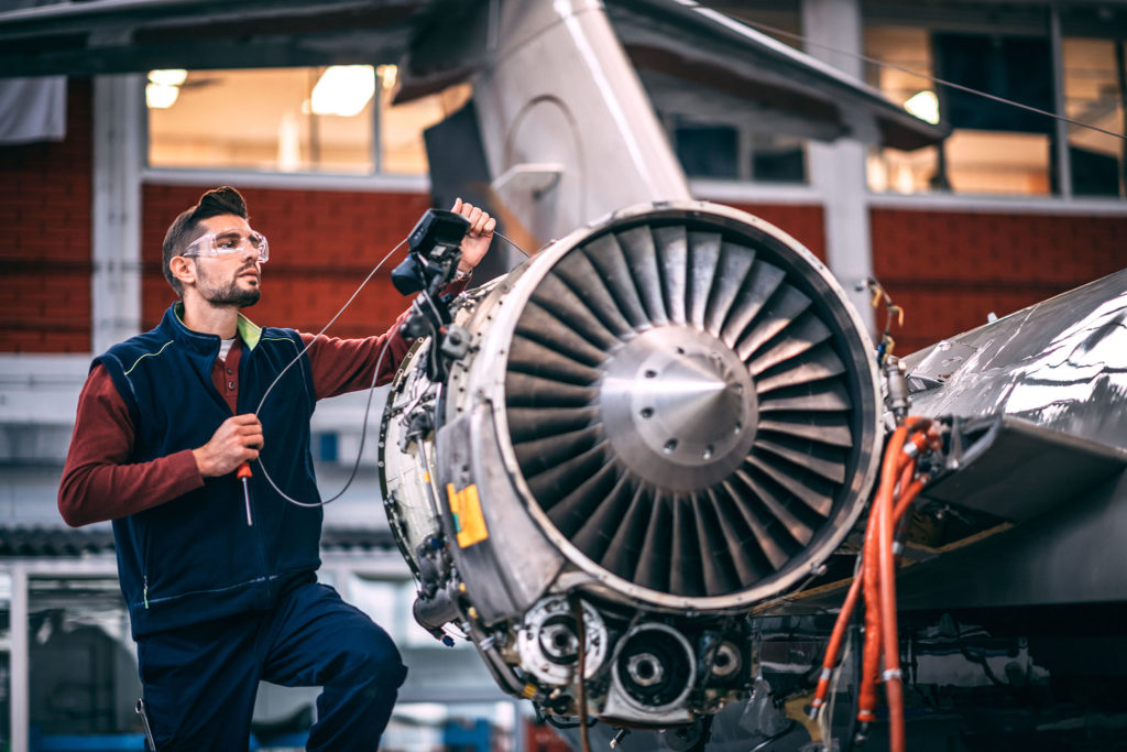 Aircraft mechanic probing an opened jet engine of an airplane