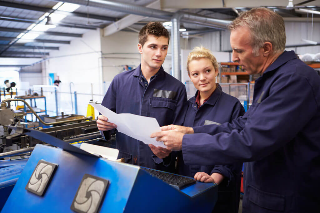 Engineer Teaching Apprentices To Use Tube Bending Machine At Work