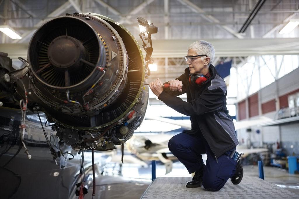 Senior female engineer in the hangar repairing and maintaining airplane jet engine